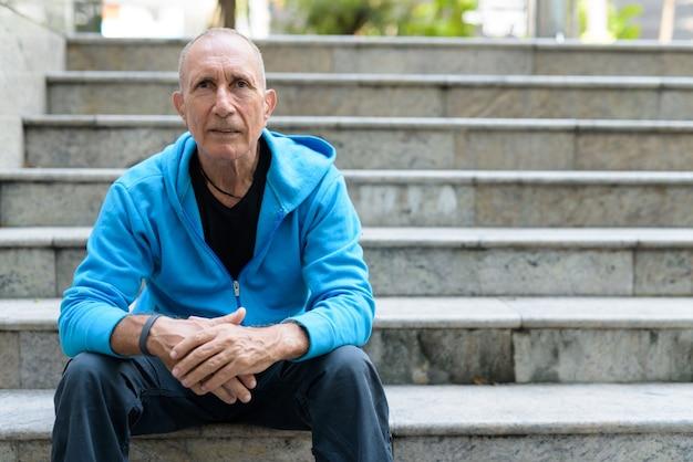 Homem calvo sênior apoiando os braços sobre os joelhos enquanto está sentado na escada