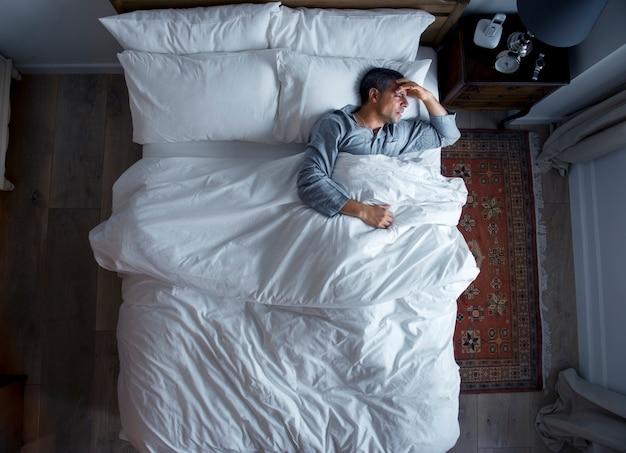 Homem, cama, dor de cabeça