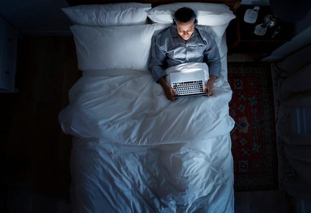 Homem, cama, usando, seu, laptop, e, um, headphone