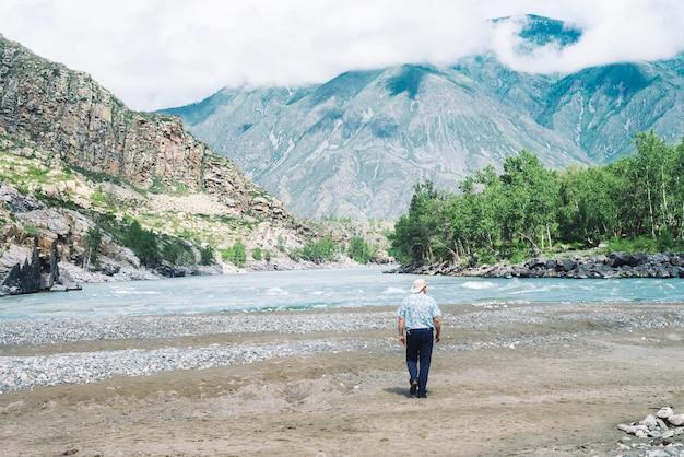 Homem caminha ao longo da areia em direção a ondas do rio da montanha em meio a montanhas gigantes e rochas na neblina
