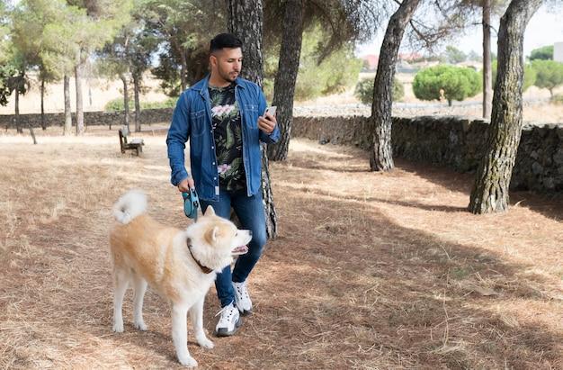 Homem caminha com seu cachorro na floresta