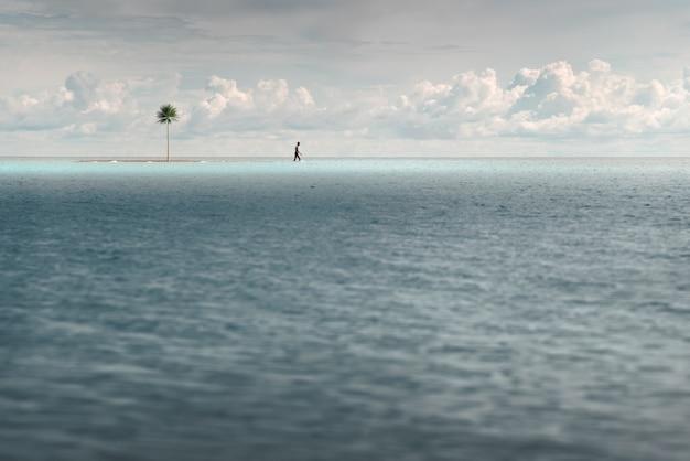 Homem caminha em águas turquesas rasas. perto de uma pequena ilha desabitada