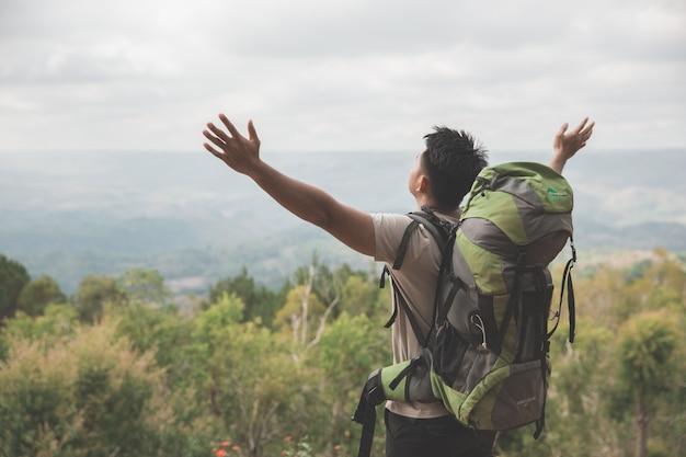 Homem caminhadas na natureza, levantar o braço