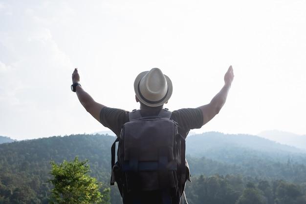 Homem, caminhadas nas montanhas do sol com mochila pesada