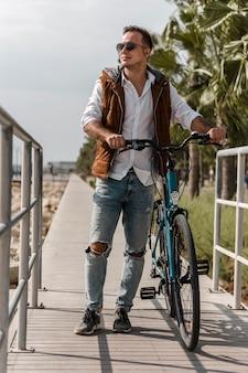 Homem caminhando ao lado de sua bicicleta