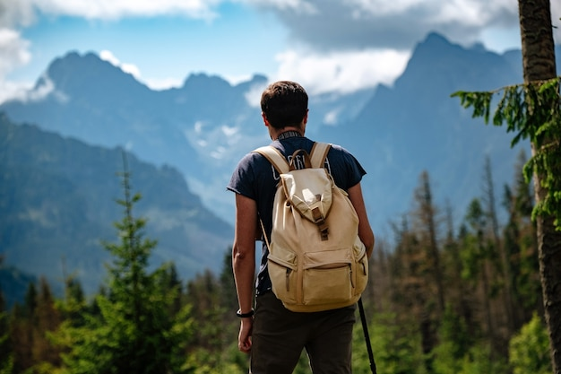 Homem caminhando em montanhas com mochila pesada