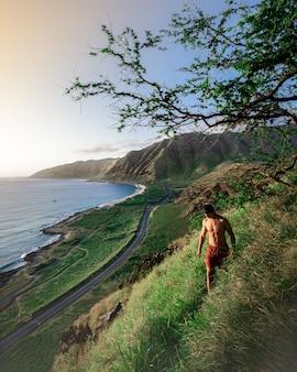 Homem caminhando em uma colina verde íngreme com o lindo mar e as colinas do