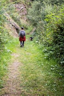 Homem caminhando na natureza com cachorro