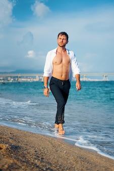 Homem caminhando na praia ao pôr do sol