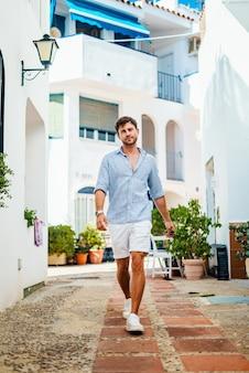 Homem caminhando na rua iluminada pelo sol