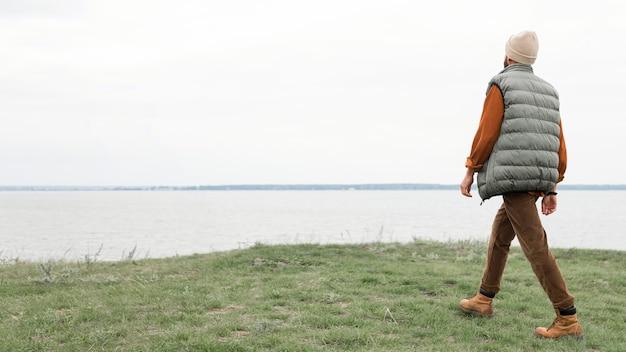 Homem caminhando no campo em direção à água