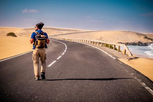 Homem caminhando no meio de uma longa estrada com deserto em ambos os lados e praia oceânica