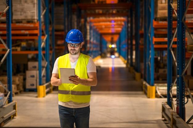 Homem caminhando pelo centro do armazém de armazenamento de um grande armazém e usando o tablet para controlar a distribuição