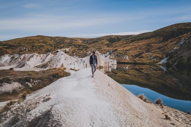 Homem caminhando perto de blue lake walk na nova zelândia cercado por montanhas