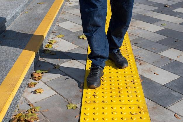 Homem caminhando sobre blocos amarelos de pavimentação tátil para deficientes visuais. blocos de grade, ladrilhos táteis para deficientes visuais, blocos tenji