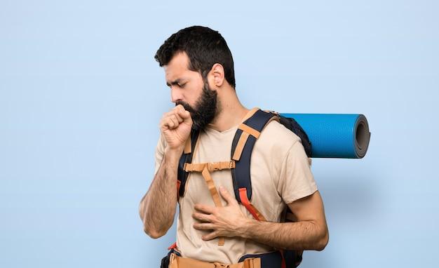 Homem caminhante está sofrendo com tosse e se sentindo mal sobre fundo azul isolado