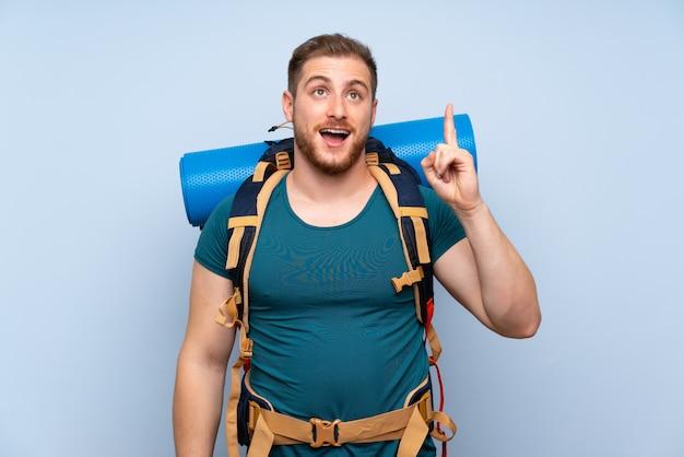 Homem caminhante sobre parede azul, pretendendo realizar a solução enquanto levanta um dedo