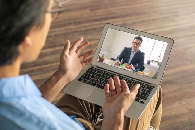 Homem, candidatando-se a um trabalho remoto. ele está fazendo sua entrevista em uma vídeo chamada.