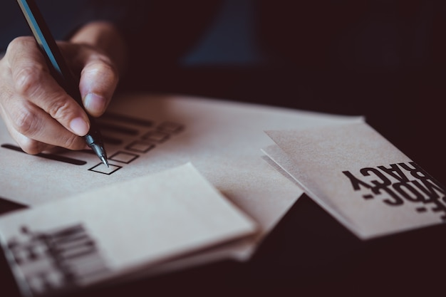 Homem, caneta segurando, marcar, voto, papel