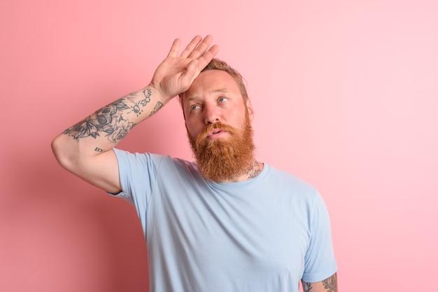 Homem cansado com barba e camiseta azul claro