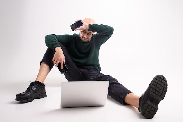 Homem cansado com dois telefones e retrato de estúdio de laptop