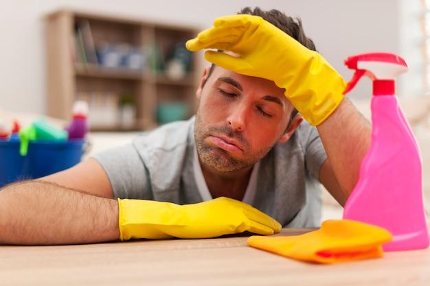 Homem cansado com equipamento de limpeza