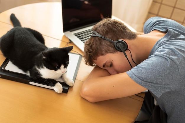 Homem cansado com gato trabalhando em casa durante a quarentena