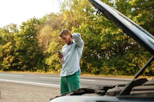 Homem cansado com o capô aberto corrige o problema do motor