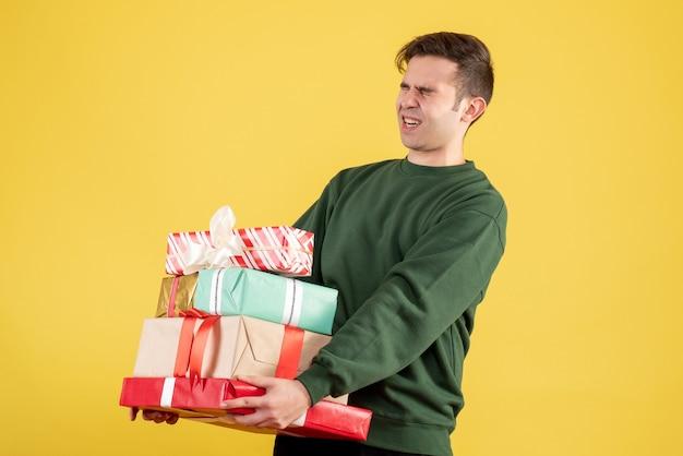 Homem cansado de vista frontal com os olhos fechados segurando presentes em pé no amarelo