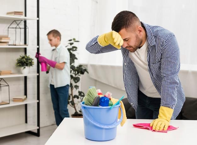 Homem cansado depois de limpar a casa