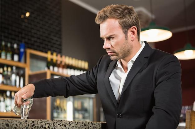 Homem cansado, derramando um tiro de álcool