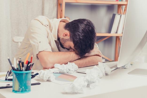 Homem cansado dormindo no trabalho, papel amassado na mesa