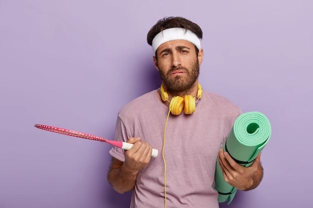 Homem cansado e ativo posando com equipamentos esportivos