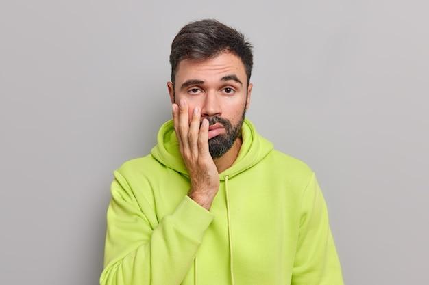 Homem cansado e chateado mantém a mão no rosto tem expressão facial entediada e desinteressada, farto de conversas enfadonhas, usa um moletom verde