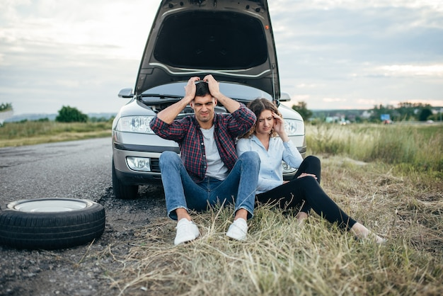 Homem cansado e mulher sentada contra um carro quebrado com capô aberto. problemas com veículo na estrada em dia de verão