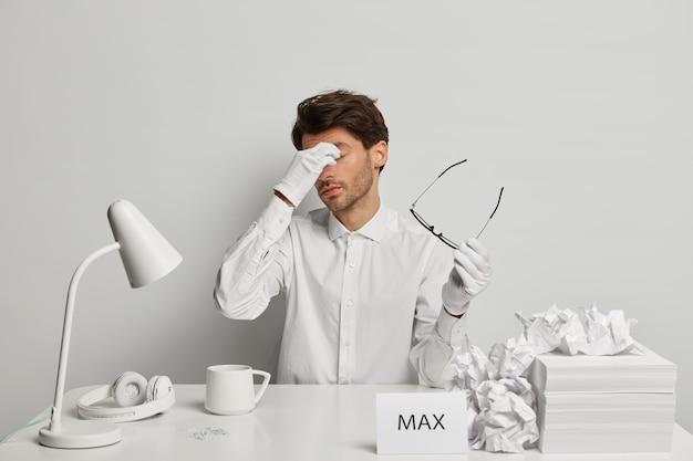 Homem cansado e sobrecarregado de roupas brancas, massageia a ponte do nariz, tira os óculos