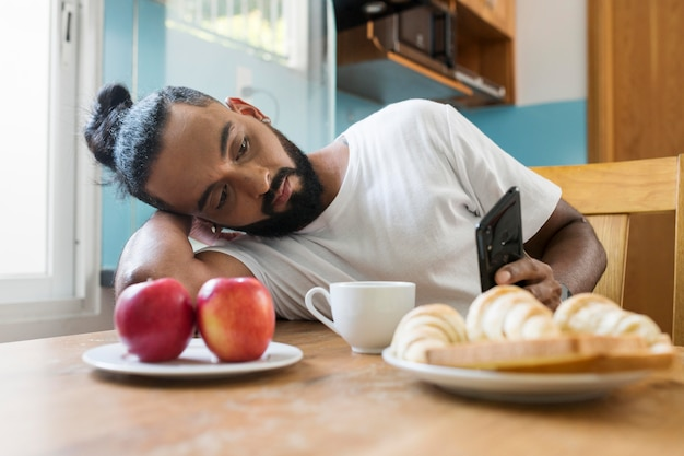 Homem cansado enquanto toma o café da manhã