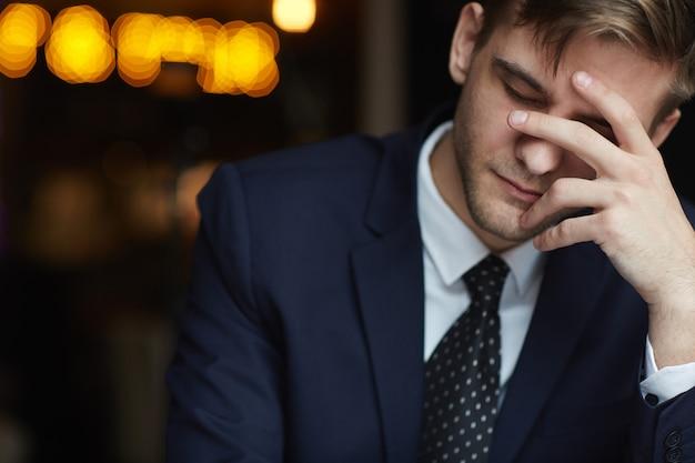 Homem cansado, esperando no café