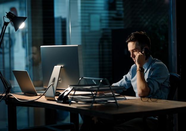 Homem cansado, falando no telefone no escritório escuro