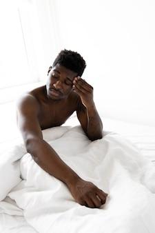 Homem cansado na cama com tiro médio