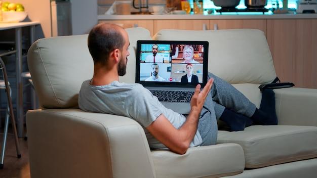 Homem cansado sentado confortavelmente no sofá enquanto conversa com colegas de equipe