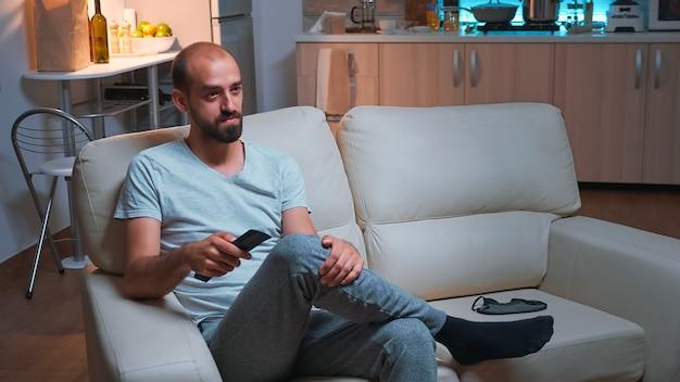Homem cansado sentado em frente à televisão assistindo a uma série de filmes de entretenimento