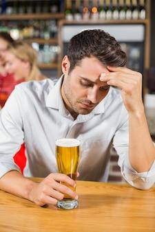 Homem cansado, sentado em um bar