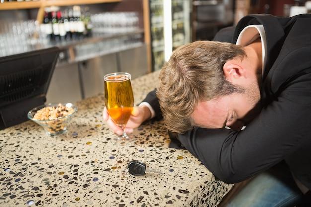 Homem cansado, tomando uma cerveja