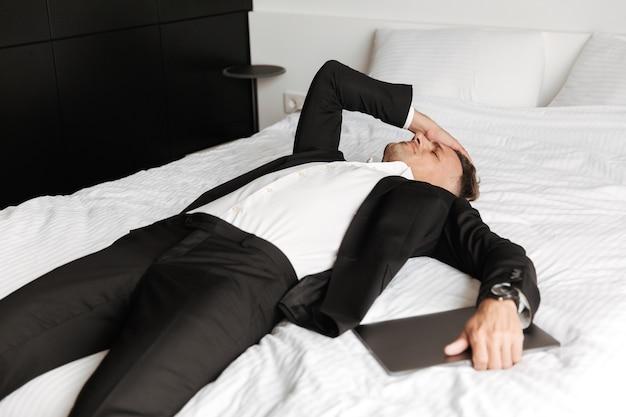 Homem cansado vestido de terno deitado na cama