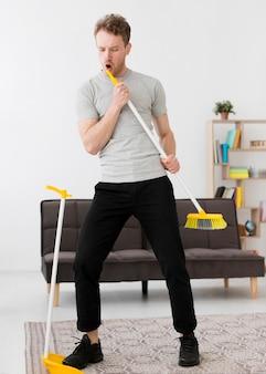 Homem cantando na vassoura durante a limpeza