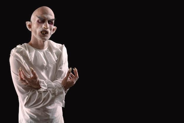 Homem caracterizado como vampiro em um fundo preto.