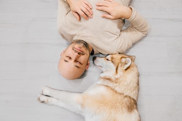Homem careca adulto com filhote de cachorro husky dormindo no chão.