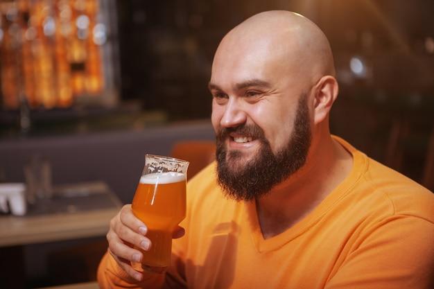 Homem careca barbudo atraente, sorrindo, tomando um copo de cerveja no pub