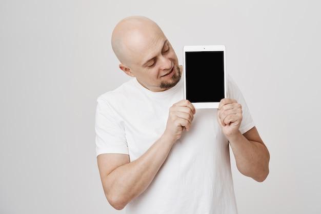Homem careca bonito de meia-idade mostrando tela de tablet